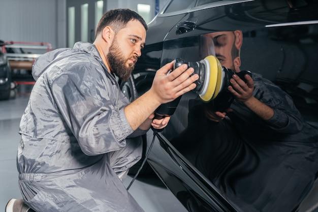 Рабочий полирует машину специальной шлифовальной машиной и воском от царапин на автосервисе