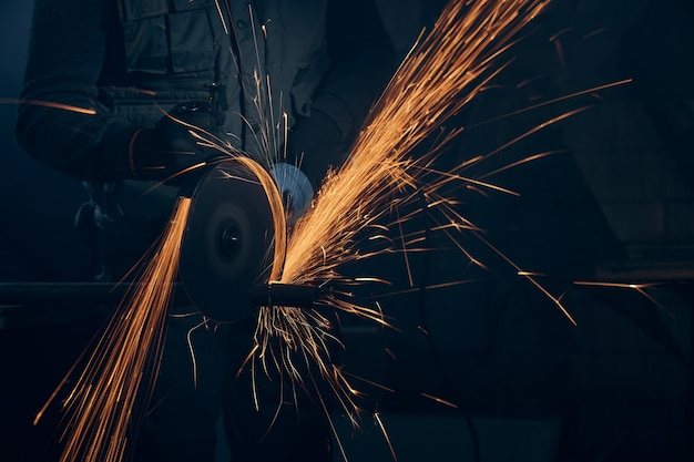 Worker polishing metal with special equipment in dark room