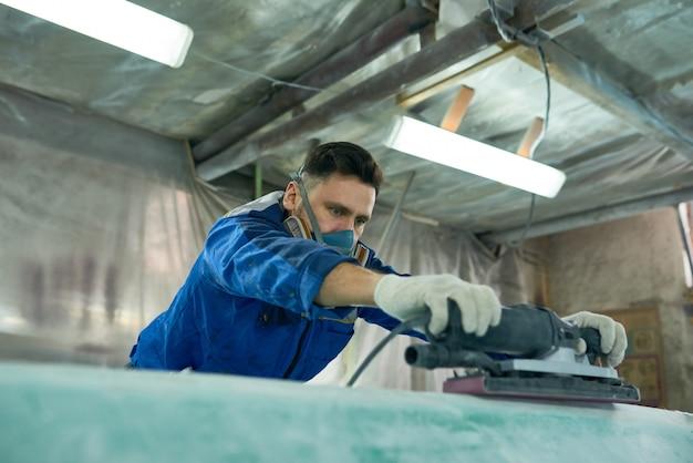 Работник полировки моторной лодки в мастерской
