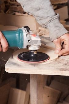Рабочий полирует деревянный стол, где плотник руками шлифует дерево с помощью электрической шлифовальной машины