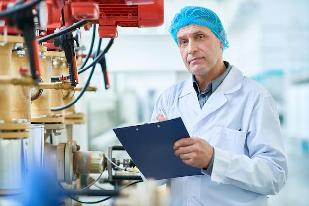 Рабочий позирует по трубам на современной фабрике
