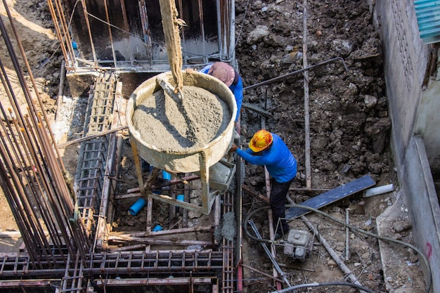 Worker pouring cement pouring into foundations formwork at building area in construction site.