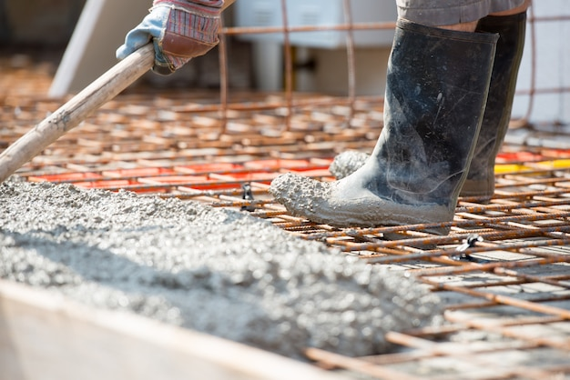 Worker pouring concrete mix at home foundation