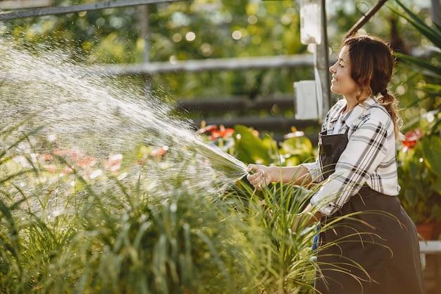 Рабочий поливает цветочные горшки. девушка в черном фартуке
