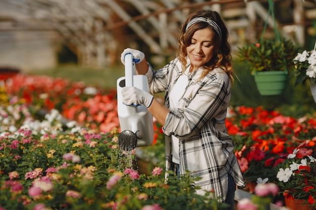 Рабочий поливает цветочные горшки. девушка в белой рубашке. женщина с воронкой