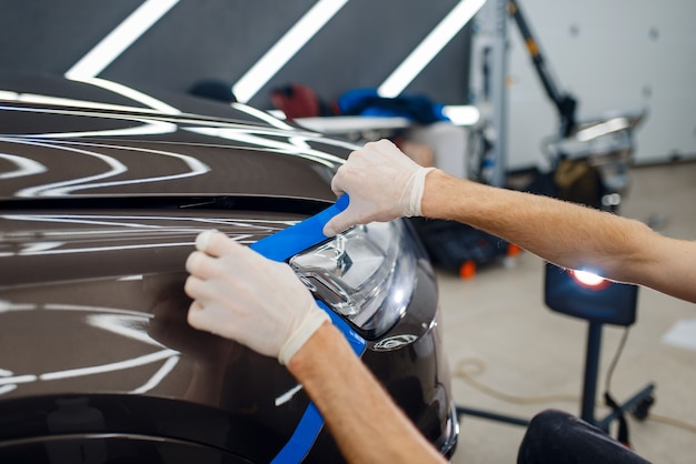 Worker prepares car to applying of protection film
