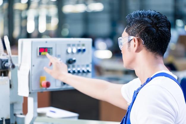 アジアの工場でcnc機械制御盤のボタンを押す労働者