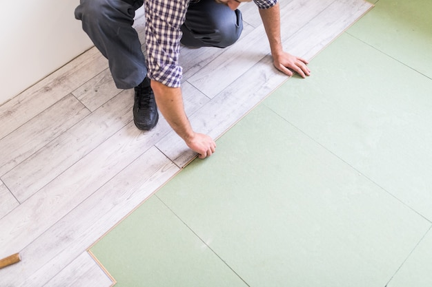 Worker processing a floor with bright laminated flooring boards