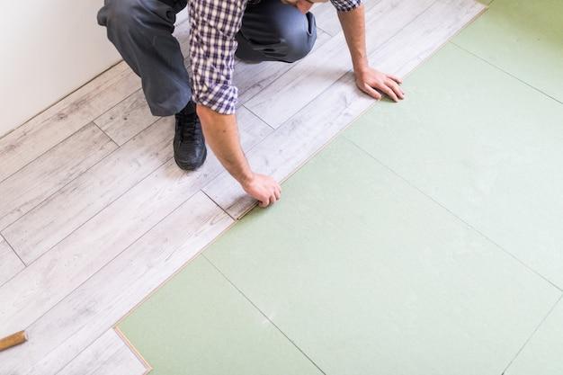 Lavoratore che elabora un pavimento con assi del pavimento laminato luminoso