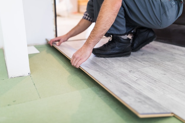 Worker processing a floor with laminated flooring boards
