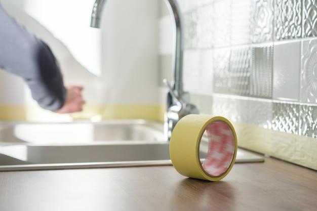 マスキングテープとキッチンのカウンタートップを保護する労働者