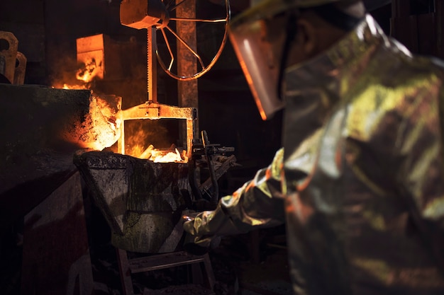 Worker in protective clothing checking molten iron in foundry.