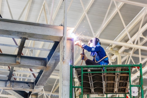 Worker in protective glasses welding for fixing steel construction frames