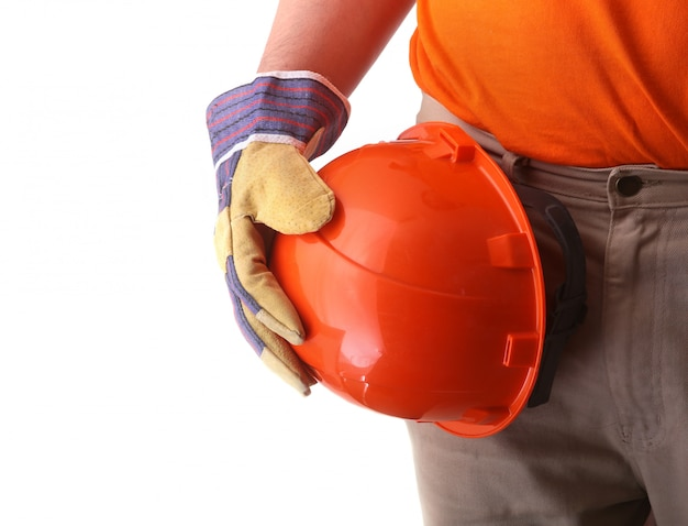 Worker in protective gloves holds an orange hard hat in his hand.