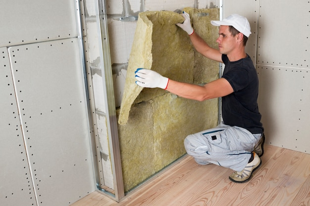 Worker in protective gloves insulating rock wool insulation in wooden frame