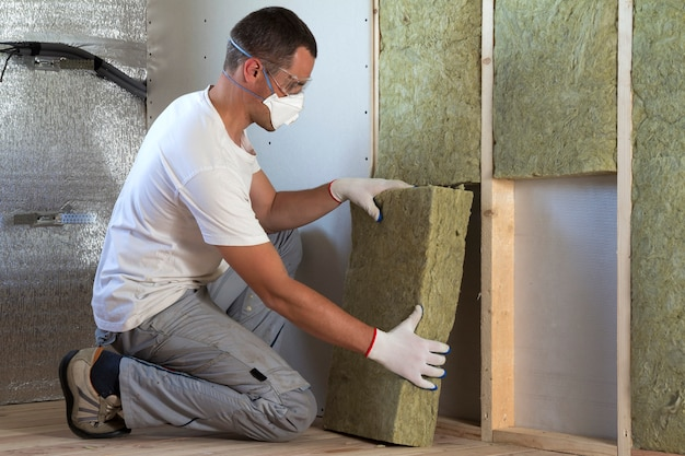 Worker in protective goggles and respirator insulating rock wool insulation in wooden frame for future house walls for cold barrier. comfortable warm home, economy, construction and renovation