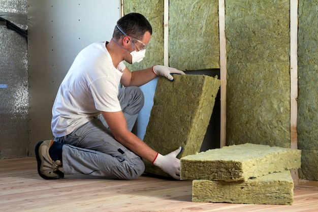 Worker in protective goggles and respirator insulating rock wool insulation in wooden frame