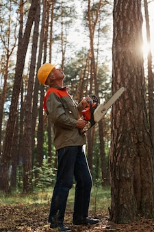 Worker in protective helmet and jacket with chainsaw looking up at high tree