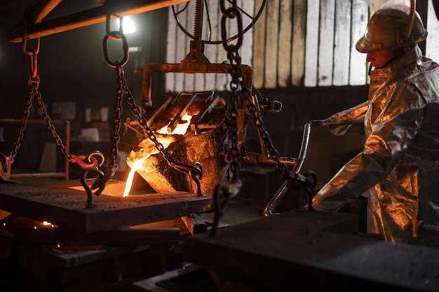 Worker in protective suit pouring molten steel into molds.