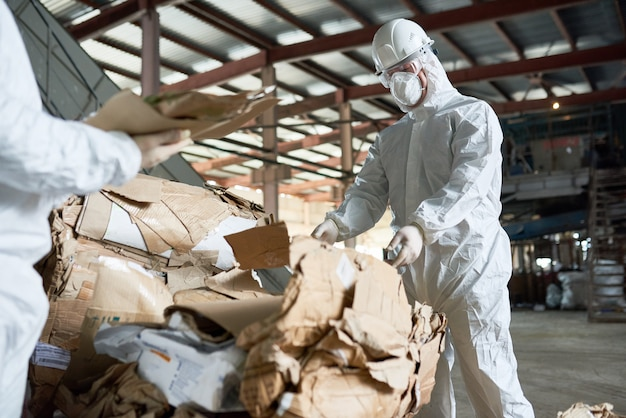 Worker in protective suit sorting cardboard at factory