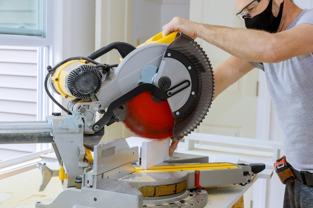The worker protects himself from covid-19, man cut using circular saw rotating saw cutting wood baseboard