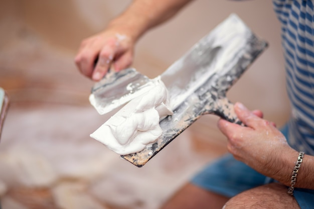 Worker puts putty on a spatula for plastering internal walls in a living room