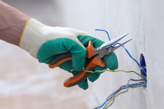 Рабочий кладет провода в стену