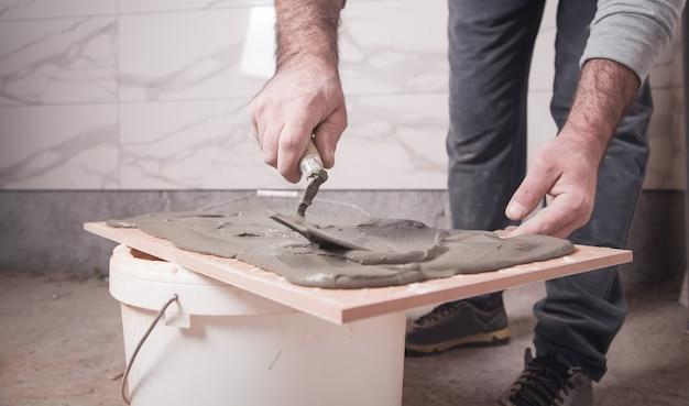Рабочий наносит клей на плитку.