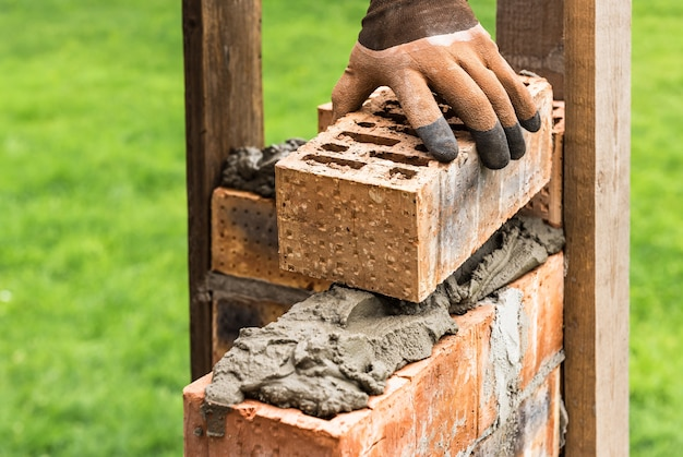 Worker putting bricks on the mortar