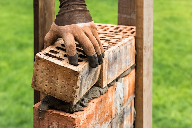 Рабочий кладет кирпичи на раствор