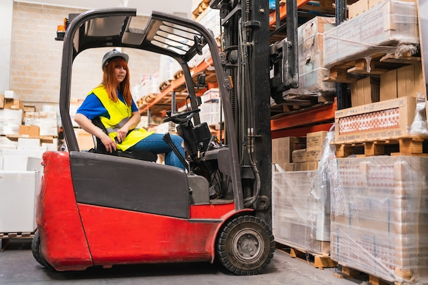倉庫でパレットを拾いながらフォークリフトのシートベルトを着用している労働者