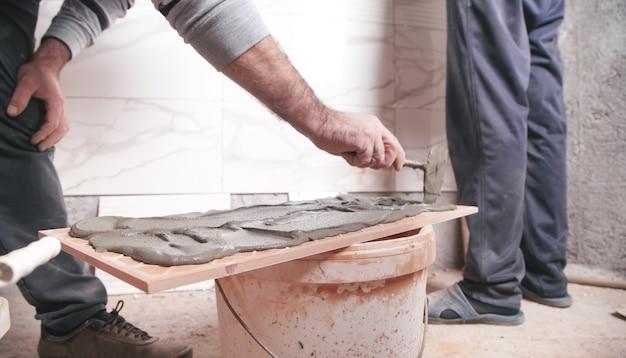 Рабочий кладет клей для плитки на стену.