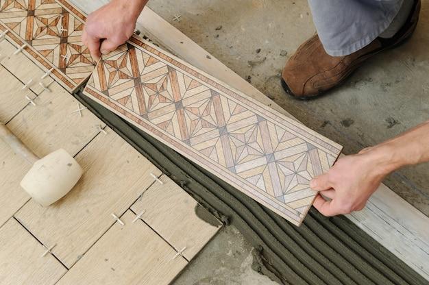 Worker putting tiles on the floor.