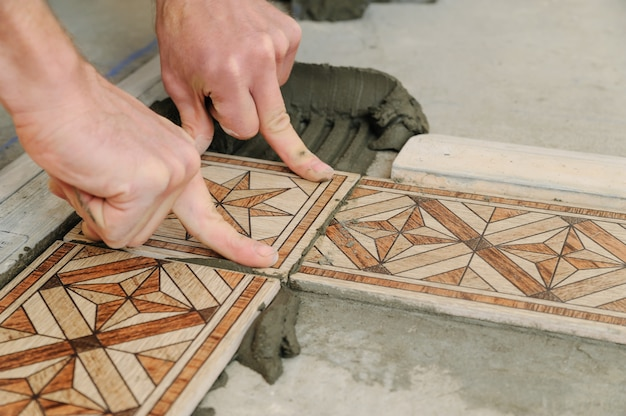 Worker putting tiles on the floor.