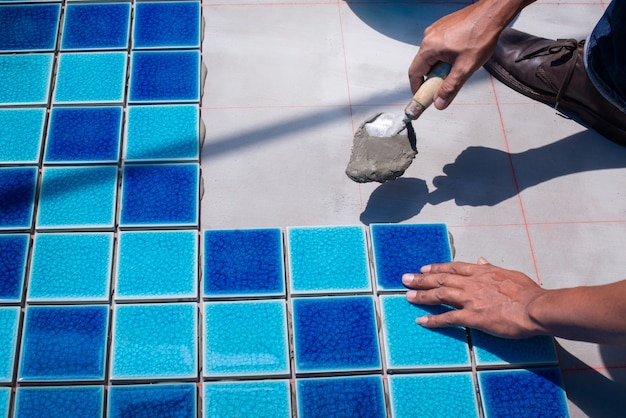 A worker putting tiles at home repair, installation of tiles on the glue, with trowel in hand