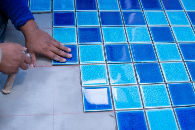 A worker putting tiles at home repair, installation of tiles on the glue