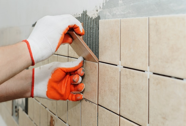 Worker  putting  tiles on the wall in the kitchen.
