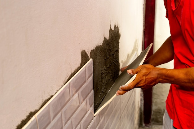 Worker putting tiles on the wall.