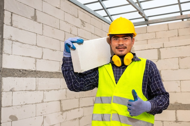 Работник успокаивает автоклавный газоблок на стройке, concept предлагает использовать автоклавный газоблок для строительства домов.