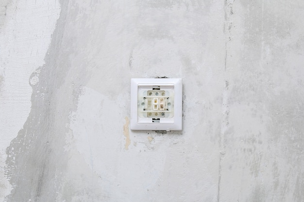 A worker removes the light switch for wallpapering.