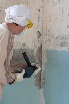 労働者は、ノミ付きロータリーハンマーでコンクリートの壁から古い塗料を取り除きます。塗料を取り除く機械的な方法、アパートの修理作業