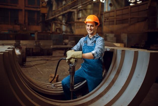 Рабочий удаляет окалину с металлических заготовок
