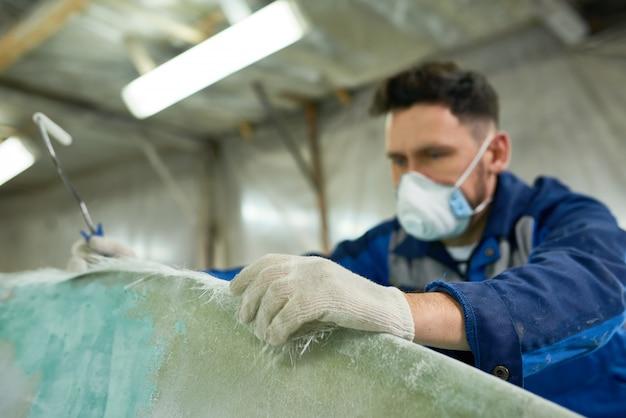 Рабочий ремонтирует лодки в мастерской