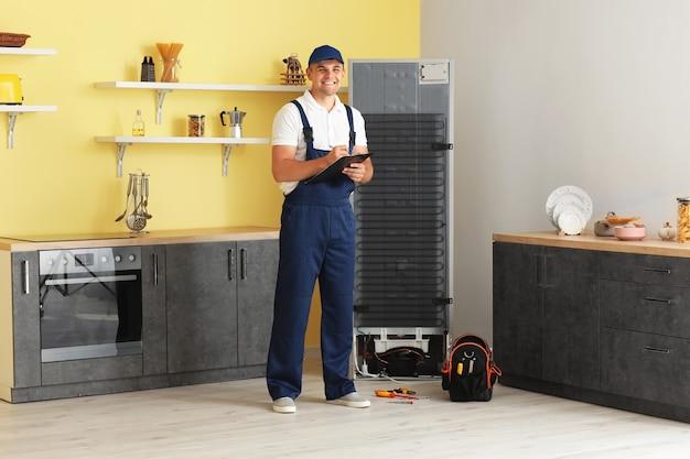 Рабочий, ремонтирующий холодильник на кухне Premium Фотографии