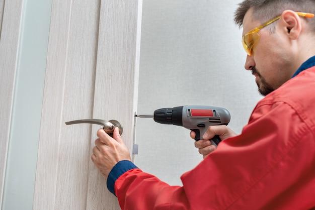 Рабочий, ремонтирующий дверную ручку с помощью отвертки