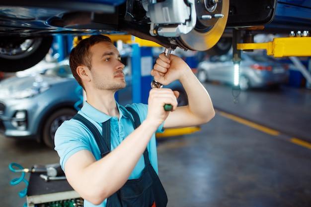 Рабочий, ремонтирующий автомобиль на подъемнике, автосервис