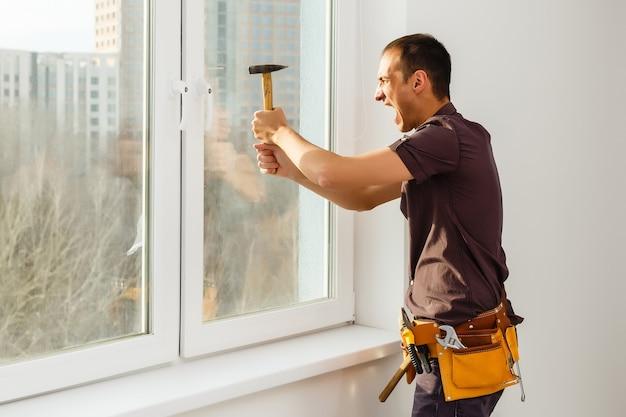 Рабочий ремонтирует окна молотком