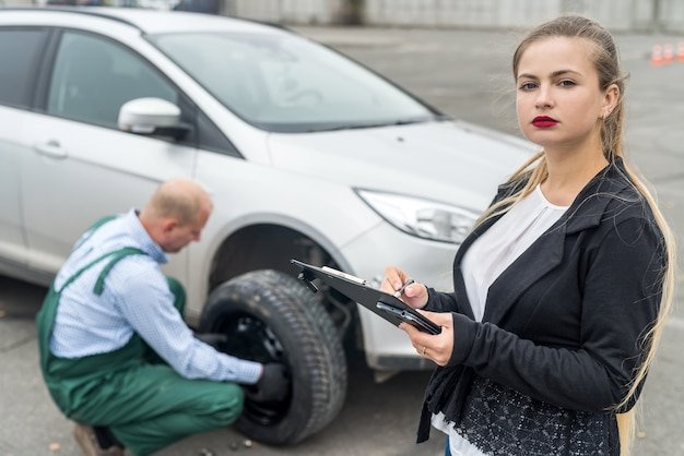 Рабочий заменяет колесо и женщина пишет в буфер обмена