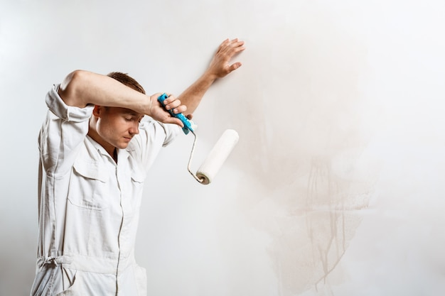 Работник отдыхает, держа ролик на белой стене.