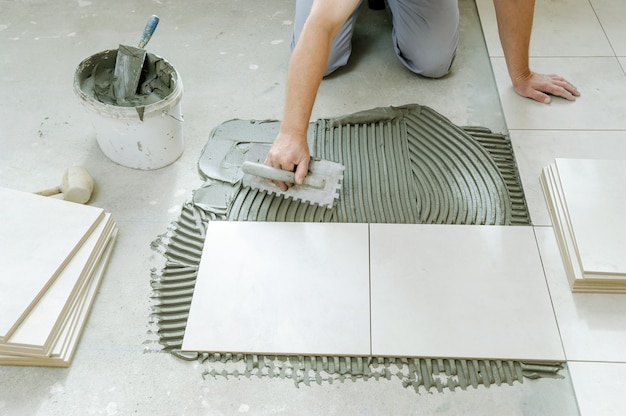 Worker's hand putting tiles adhesive to floor with notched trowel